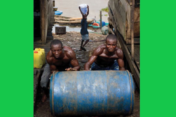 Young men struggle with a barrel of petrol in Yenagoa, near Oloibiri. Most inhabitants of the Niger Delta do not have access to reliable and affordable energy. Photo by Ed Kashi